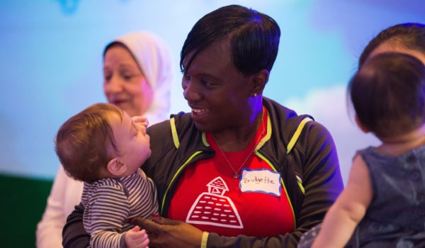 KinderCare teacher, Bridgette, charms an infant