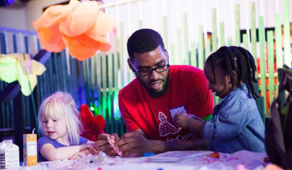 KinderCare teacher, Carter, helps children with an activity