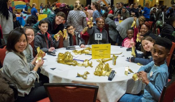 Enthusiastic volunteers create gold awareness ribbons for the American Childhood Cancer Association